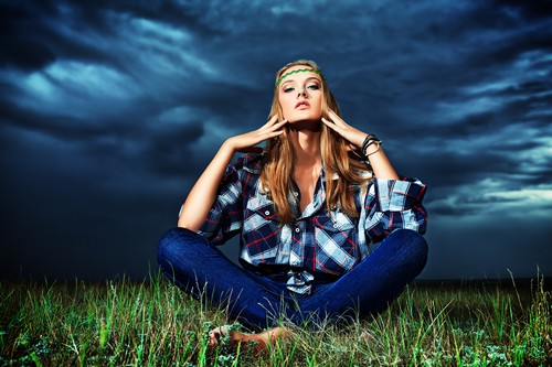 Romantic young woman in casual clothes sitting in a field on a background of the storm sky.