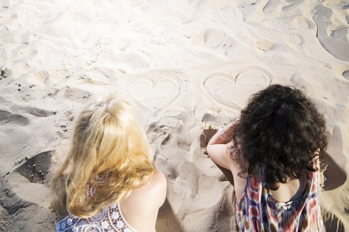 Two young womans draw hearts on warm sand